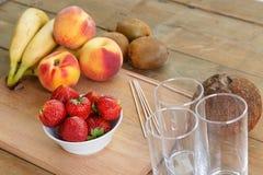 Bringen Sie für Fruchtcocktail auf ein Schneidebrett Erdbeeren, Bananen, Pfirsiche, Kiwis unter Stockfotografie