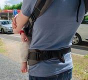 Bringen Sie Griffkind im Babyriemen auf der Straße hervor Rückseitige Ansicht lizenzfreies stockfoto