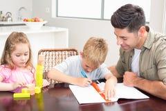 Bringen Sie helfenden Sohn mit Hausarbeit mit dem kleinen Mädchen hervor, das mit Blöcken spielt Stockbilder