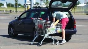 Bringen Sie Ladennahrungsmittel vom Warenkorb in Autokofferraum am Parkplatz hervor Die Rolle von Männern in der Familie Verteilu stock footage