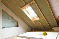 Bringen Sie Mansarden-Wandisolierung des Dachbodens im Bau mit Felsen unter stockbilder