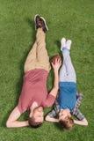 Bringen Sie mit dem Ball und kleinem Sohn hervor, die auf das Gras am Hinterhof legen lizenzfreie stockfotografie
