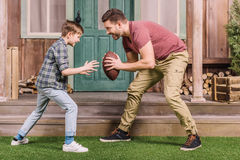 Bringen Sie mit dem kleinen Sohn hervor, der amerikanischen Fußball mit Ball am Hinterhof spielt Stockfotografie
