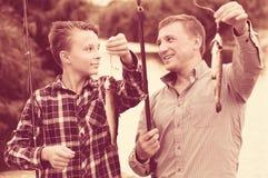 Bringen Sie mit dem Sohn hervor, der Fische auf Haken betrachtet Lizenzfreie Stockfotos