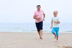 Bringen Sie mit dem Sohn hervor, der Spaß auf dem Strand hat Stockbilder
