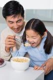 Bringen Sie mit der jungen Tochter hervor, die Getreide in der Küche isst Stockfotografie