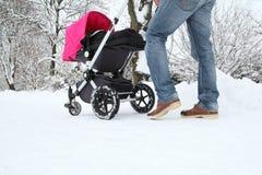 Bringen Sie mit seinem Baby in einem Buggy auf einer schneebedeckten Bahn hervor lizenzfreie stockfotos