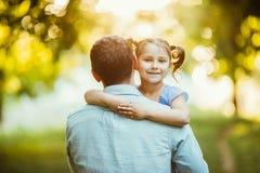 Bringen Sie mit seinem Doughter in den Händen hervor, die in Sommerparksonnenuntergang gehen Glückliches Tochterlächeln stockfotografie
