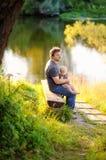 Bringen Sie mit seinem kleinen Baby hervor, das auf Holzbank sitzt Stockfoto