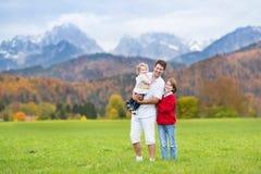 Bringen Sie mit seinen Kindern in Berg bedecktem Schnee hervor Stockfotografie