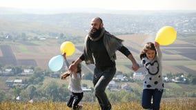 Bringen Sie mit seinen zwei Töchtern mit den Ballonen einer Luft hervor, die in die Wiese laufen stock video footage