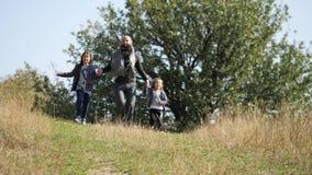 Bringen Sie mit seinen zwei Töchtern hervor, die vom Hügel an der Kamera laufen stock video footage