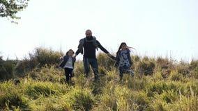 Bringen Sie mit seinen zwei Töchtern hervor, die vom Hügel an der Kamera laufen stock video