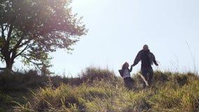 Bringen Sie mit seiner Tochter hervor, die vom Hügel läuft stock video