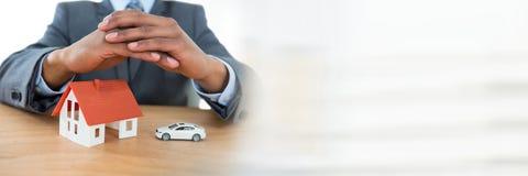 Bringen Sie Modell und Auto unter schützenden Händen eines Geschäftsmannes unter Stockfotos