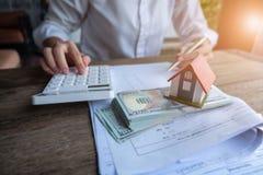 Bringen Sie Modell und Geld in der Hand, Konzept von Immobilien und Abkommen unter stockfoto