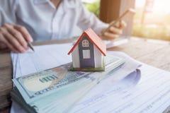 Bringen Sie Modell und Geld in der Hand, Konzept von Immobilien und Abkommen unter lizenzfreies stockfoto