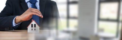 Bringen Sie Modell unter schützenden Händen eines Geschäftsmannes unter Lizenzfreie Stockfotografie