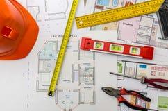 Bringen Sie Projektzeichnungen mit Sturzhelm, Maurerwerkzeuge unter stockfoto