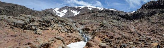 Bringen Sie Ruapehu-Landschaft und kleines watefall an, die unter eine Schneekappe in Nationalpark Tongariro fließen Stockbild