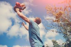 Bringen Sie seine Tochter auf dem Gebiet draußen spielen und fangen hervor stockbild