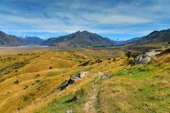Bringen Sie Sonntag und umgebende Gebirgszüge an, benutzt in Schmierfilmbildung Lord der Ringfilm Edoras-Szene, in Neuseeland Stockbilder