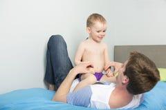 Bringen Sie Spiel mit seinem Sohnjungen auf dem Bett zu Hause hervor stockfotografie