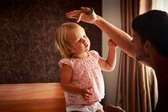 bringen Sie Spiele mit kleiner Tochter im Rosa hervor und macht Haar glatt Stockbild