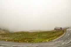 Bringen Sie Stellung auf einem Berg in den Wolken unter Stockfotografie