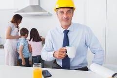 Bringen Sie tragenden Hardhat und trinkenden Kaffee zu Hause mit seinem fami hervor Stockbild