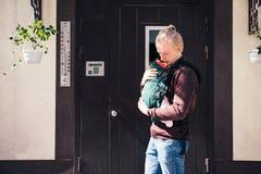 Bringen Sie tragendes Baby im Riemen oder ergo im Rucksack hervor lizenzfreie stockfotos