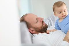 Bringen Sie und ein Baby hervor, das auf das Sofa streichelt Stockfotografie