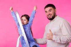 Bringen Sie und ihre kleine Tochter mit den Daumen oben über rosa Hintergrund hervor Erwachsener Mann und Baby sind glücklich lizenzfreies stockfoto