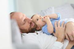 Bringen Sie und sein Baby hervor, das auf einem Sofa sich entspannt Lizenzfreies Stockbild