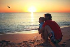 Bringen Sie und sein kleiner Babysohn hervor, der auf Sonnenuntergangstrand sitzt Familie V Lizenzfreies Stockfoto