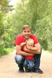 Bringen Sie und sein Kleinkindsohn fave Spaß im Sommerpark hervor Vati, der den Sohn im Freien umarmt Familienblickkleidung Kopie Stockfotos
