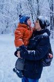 Bringen Sie und sein Sohn hervor, der draußen spielen, Winterwald auf dem Hintergrund und schneien, glücklich und froh stockbilder