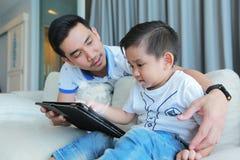 Bringen Sie und sein Sohn hervor, der Spaß durch Spiel auf einer Tablette habend glücklich ist stockfotografie