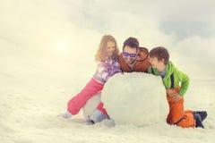 Bringen Sie und sein Sohn und doughter hervor, die einen Schneemann errichten Stockfotos