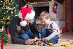 Bringen Sie und sein Sohnspiel mit Modelleisenbahn nahe Weihnachtsbaum hervor Stockbilder