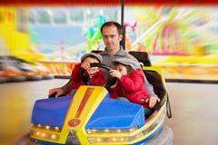 Bringen Sie und seine zwei Söhne hervor und eine Fahrt im Autoskooter haben Lizenzfreies Stockbild