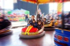 Bringen Sie und seine zwei Söhne, L hervor, das eine Fahrt im Autoskooter an hat Lizenzfreies Stockfoto