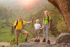 Bringen Sie und zwei Kinder mit Rucksäcken auf schöner Natur hervor Lizenzfreie Stockbilder
