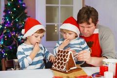 Bringen Sie und zwei kleine Söhne hervor, die ein Lebkuchenplätzchenhaus vorbereiten Lizenzfreies Stockbild