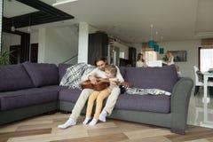 Bringen Sie unterrichtende Sohnspielgitarre, helfende Mutter der Tochter auf kitc hervor lizenzfreie stockbilder
