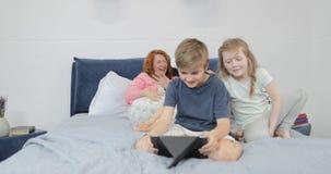 Bringen Sie versuchende Gläser der virtuellen Realität während der Sohn hervor, der zusammen Tablette im Schlafzimmer, Familie zu stock video