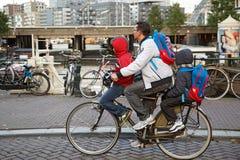 Bringen Sie zwei Kinder auf dem Fahrrad auf einmal tragen hervor Amsterdam, die Niederlande lizenzfreie stockfotografie