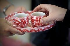 Bringen traditionelle rote Teeschalen der chinesischen Hochzeitsteezeremonie auf Behälterbrautumhüllung hervor Stockfoto