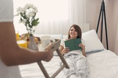 Bringing breakfast on a tray. Happy and surprised young women lying in bed in the morning while her husband is bringing her breakfast and flowers on a tray Stock Photo