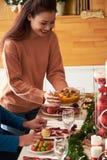 Bringing dish to Christmas table stock photo